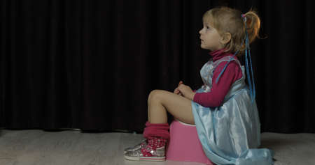 Photo pour Little girl sitting on the potty and watching TV. Blonde cute child in blue dress. Inside - image libre de droit