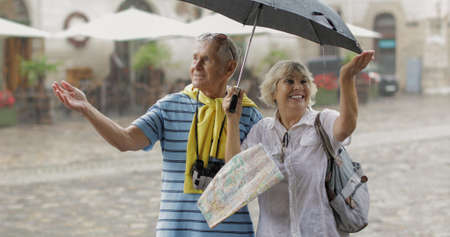 Happy senior two male and female tourists stand downtown and enjoy the rainy weather while traveling in Lviv, Ukraine. Elegant woman with bag. A man with binoculars. Vacation concept