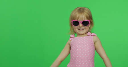 Foto de Child in pink swimsuit and sunglasses. Happy, pretty little blonde girl, 3-4 years old. Make faces and smile. Summer vacation concept. Green screen. Chroma Key - Imagen libre de derechos