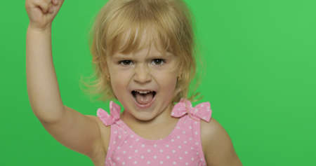 Foto de Girl emotionally make faces and show anger in pink swimsuit. Portrait close up. Angry, cute little blonde child, 3-4 years old. Green screen. Chroma Key - Imagen libre de derechos