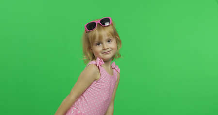 Photo for Child in pink swimsuit and sunglasses. Happy, pretty little blonde girl, 3-4 years old. Make faces and smile. Summer vacation concept. Green screen. Chroma Key - Royalty Free Image