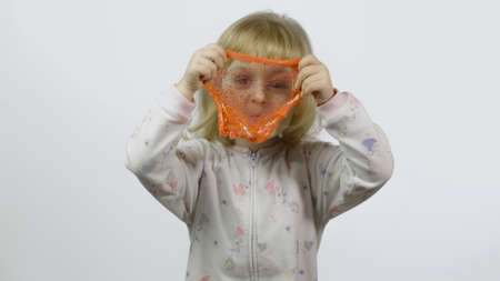 Child having fun making orange slime. Kid playing with hand made toy slime. Funny kid girl. Relax and Satisfaction. Oddly satisfying orange slime for pure fun and stress relief. White background