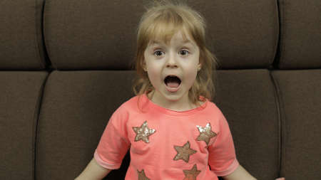 Foto de Positive girl on sofa at home emotionally make faces and smile in pink blouse with stars. Portrait close up. Happy, cute little blonde child, 4-5 years old - Imagen libre de derechos