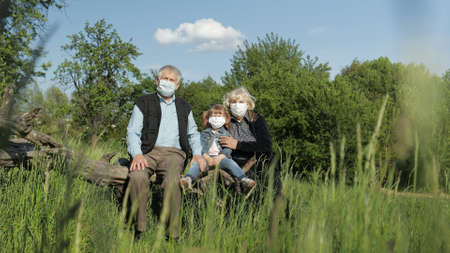 Photo for Grandparents with granddaughter together sitting in spring park in medical masks. Coronavirus covid-19 pandemia quarantine. Family time together. Grandfather, grandmother, girl child sitting together - Royalty Free Image