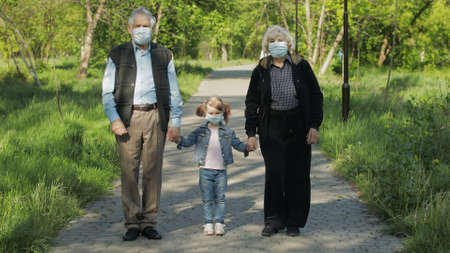 Photo pour Old grandparents with granddaughter together walk in spring park in medical masks. Coronavirus covid-19 pandemia quarantine. Family time together. Grandfather, grandmother, girl child holding hands - image libre de droit