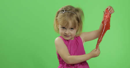 Child having fun making red slime. Kid playing with hand made toy slime. Funny kid girl. Relax and Satisfaction. Oddly satisfying blue slime for pure fun and stress relief. Green screen. Chroma Key