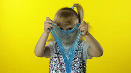 Child having fun making turquoise slime. Kid playing with hand made toy slime. Funny pupil girl. Relax and satisfaction. Oddly satisfying green slime for pure fun and stress relief. Yellow background