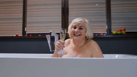 Photo pour Sexy senior woman grandmother is taking foamy bath, drinking champagne in luxury bathroom with candles. Elderly lady grandma drinks white wine. Spa procedures self-care. Skin care. Life of retirees - image libre de droit