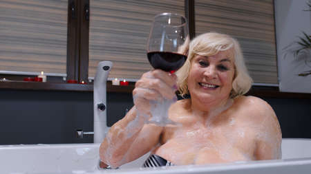 Photo pour Attractive active senior woman lying in warm bath with bubbles, enjoying relaxation, drinking red wine. Cheerful happy elderly grandmother at luxury home bathroom in a romantic setting with candles - image libre de droit