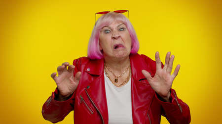 Photo pour Mature old granny gray-haired grandmother emo making playful silly facial expressions and grimacing, fooling around, showing tongue. Senior woman rocker isolated on yellow background. People lifestyle - image libre de droit