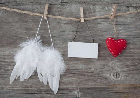Angel wings with heart and blank note on grey wooden background