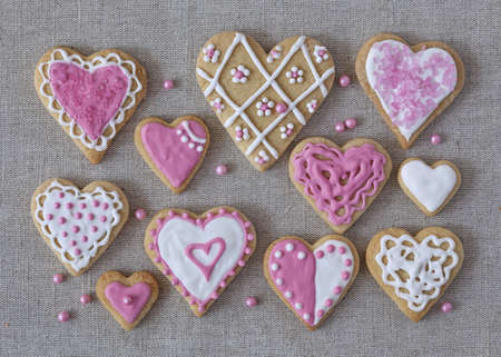 White and pink heart cookies on a grey fabric background