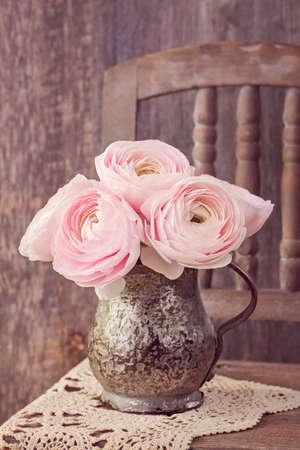 Ranunculus flowers in a old vase