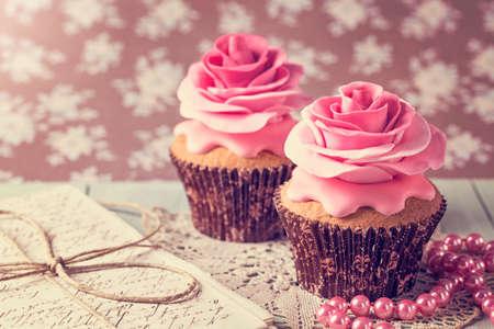 Photo pour Cupcakes with sweet rose flowers and a letter - image libre de droit