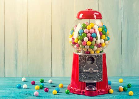 Foto per Carousel Gumball Machine Bank on a wooden background - Immagine Royalty Free