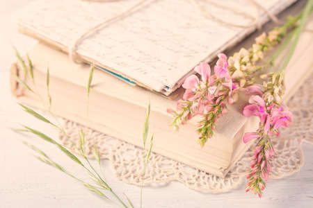 Photo pour Old book and flowers on the table - image libre de droit