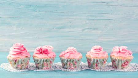 Photo pour Pink  cup cakes on a blue background - image libre de droit