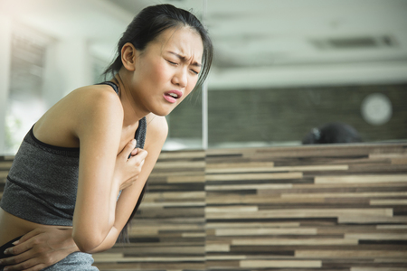 Asian woman having heart attack after workout at the gym.