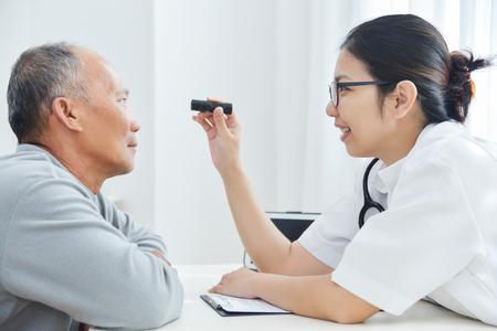 Foto de Young Asian Female Doctor wear glasses checking senior man patient eyes with flashlight in medical office. - Imagen libre de derechos