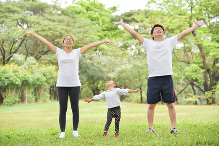 Foto de Happy Asian family with their daughter in white shirt workout at the park. People are warming up and stretching their arms at outdoors on morning. Health care concept.  Copy space. Exercising. - Imagen libre de derechos