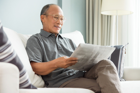 Happy Asian senior man sitting and reading newspaper at his house. Relaxing, Smiling, Retirement.