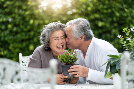 Foto de Portrait of Asian Senior man kissing his wife. Older Couple enjoying with planting flower in the garden. Retirement. - Imagen libre de derechos
