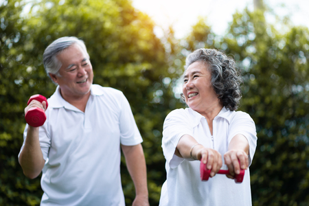 Photo pour Asian Senior Couple exercising with red dumbbells at the outdoor park togetherness. Smiling Chinese or Thai or Japanese people. - image libre de droit