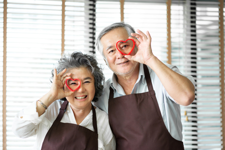 Foto de Having Fun with baking. Portrait Asian senior couple wear brown aprons are holding red cookies cutters in heart shape over their eyes. Looking at the camera. - Imagen libre de derechos