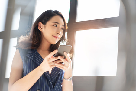 Photo for Modern Asian business woman is using cell phone in the office. Attractive Female designer smiling and standing near a window. - Royalty Free Image