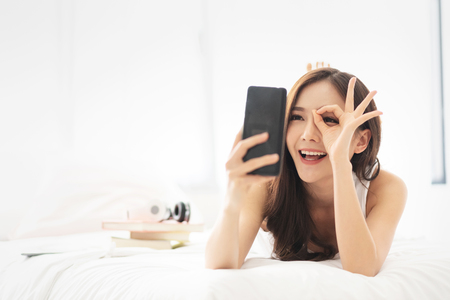 Photo pour Happy Asian Beautiful female having fun with cell phone or mobile phone while lying on her bed. Cheerful girl is making video call with smartphone at her white bedroom. Communication with technology. - image libre de droit