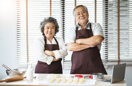 Foto de Portrait of Smiling Asian senior couple in brown aprons standing with arms crossed, Grandfather and Grandmother preparing for baking cookies on the holiday. Looking at the camera - Imagen libre de derechos