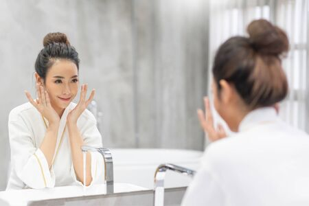 Photo for Close up beauty portrait of a laughing beautiful woman applying foam for washing on her face and looking at the mirror. Skincare spa relax. Morning and night cream. - Royalty Free Image