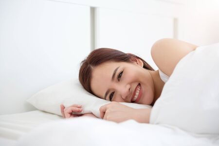 Photo for Smiling Asian beautiful woman waking up on her bed at her bedroom on the holiday. Young attractive Female with positive feeling on morning at her house. - Royalty Free Image