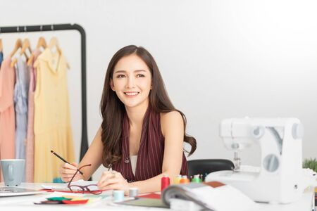 Foto de Successful of Young woman Fashion Designer is sitting and smiling. Happy, Relaxing Asian Female is working at her office. Startup Small business entrepreneur, SME. - Imagen libre de derechos