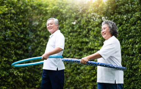 Foto de Asian Senior Couple in white shirt exercising with hula hoops at outdoor park together. - Imagen libre de derechos