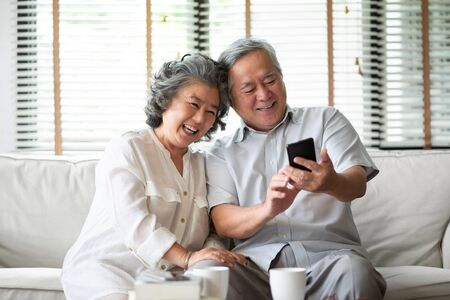 Photo pour Asian senior Couple Laughing and using cell phone technology at their home. - image libre de droit
