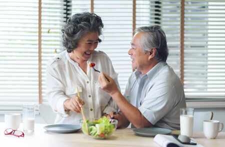Photo pour Happy Asian Senior couple doing and eating healthy salad at their house together. Lover, Retirement, Wellness. - image libre de droit