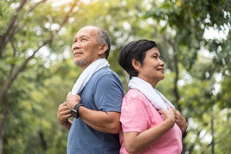 Foto de Portrait of Asian Senior couple standing over green nature background. Elderly Man and woman exercising at park outdoor together. - Imagen libre de derechos