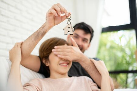 Photo pour Young man surprising woman with a key of their new house. Male closing his girlfriend eyes. Feeling of happiness. - image libre de droit