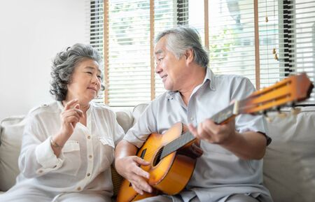 Photo for Romantic Asian senior Couple singing and playing acoustic guitar together. Happy Smiling Elderly Guitarist man and Old Vocalist woman having fun and enjoying their Retirement life. Lifestyle, Instrument, Party. - Royalty Free Image