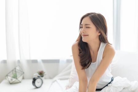 Foto de Beautiful Asian Smiling woman with eyes closed relaxing in bed at home. Portrait of Happy Charming Shy girl in white pajamas with long hair wake up and breathing air on morning. Carefree, Positive emotion, Expression face. - Imagen libre de derechos