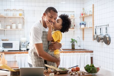 Photo pour African Cute little boy in yellow casual kissing Dad while cooking at home together. Happy smiling African-American Father while hug and carry his son in kitchen. Joyful Black family, Love emotion. - image libre de droit