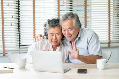 Foto de Happy Asian Senior Couple making video chat and waving hands to their family on laptop at home. Smiling Elderly man and woman enjoy with internet technology on notebook together, Mature lifestyle - Imagen libre de derechos