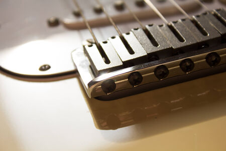 close up of the bridge of a strat, daytime,  white guitar