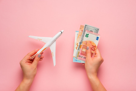 Plane and money in hand on a pink background.  Travel concept