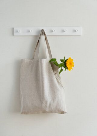 Photo for Young Yellow Sunflower in Textile Eco Bag Hanging on Hook Isolated on White Wall Background Copy Space. Blank Canvas Recycle Reusable Shopping Sack. Natural Organic Material Packaging - Royalty Free Image