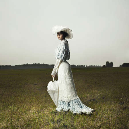 Slender woman in vintage dress for promenade