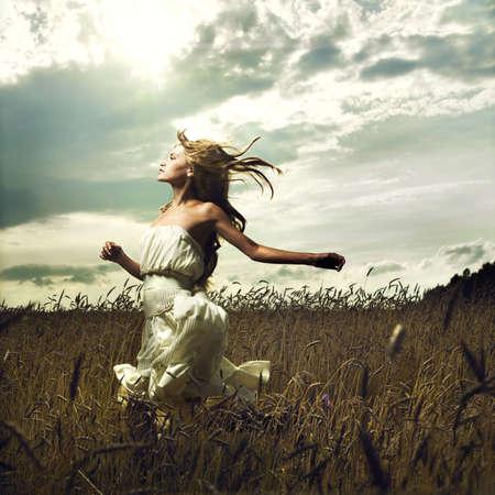 Foto de Portrait of romantic woman running across field - Imagen libre de derechos