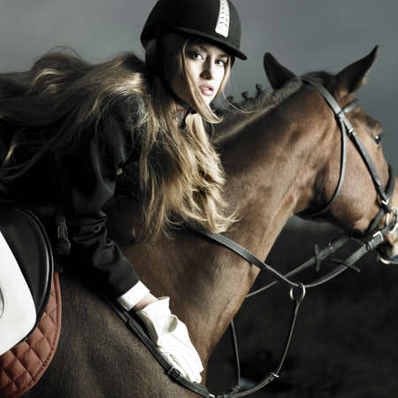 Elegant woman in a black coat riding on a brown horse