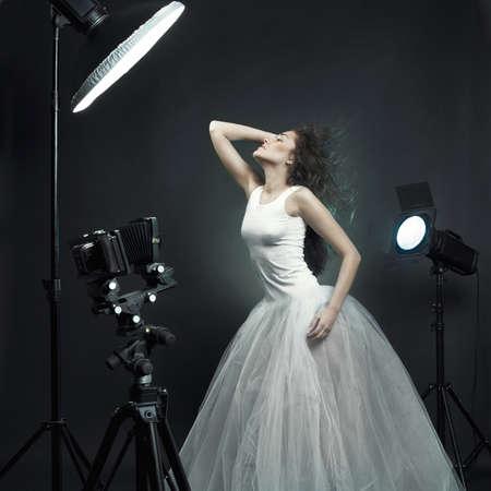 Beautiful young woman in white dress pose in studio
